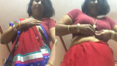 Desi female in a red sex sari flashes her XXX jugs changing the clothes